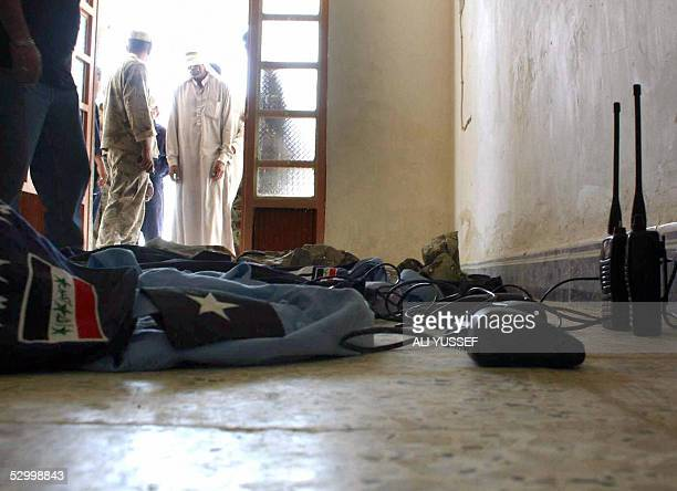 Iraqi army and police uniforms and walkie-talkies are put on display as a detainee is brought in blindfolded, following raids in the Khan Beni Saad...