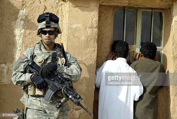Iraqi boys look from the window at US soldiers searching inside a house the northern village of Sakar near the Syrian border 04 April 2006 Iraqi...