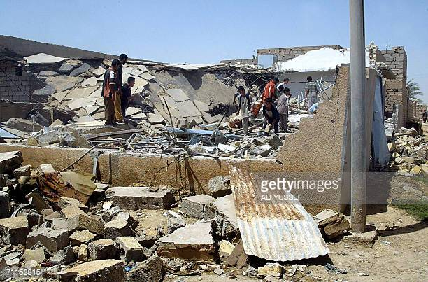 Iraqi children search among the rubble 08 June 2006 of one of four houses believed to be destroyed by US forces in the town of Hibhib north of the...