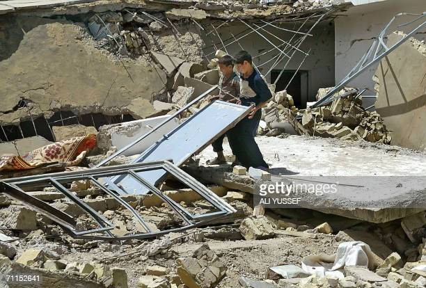 Iraqi children stand among the rubble 08 June 2006 of one of four houses believed to be destroyed by US forces in the town of Hibhib north of the...