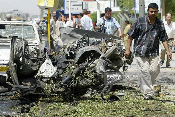 Iraqi civilians check the wreckage of a car that was destroyed in a suicide car bomb explosion in alMansour district west of Baghdad 11 May 2005 At...