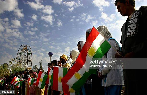 Iraqi Kurds raise the Kurdish flags during a political rally 21 November 2005 to announce the formation of a new Kurdish election alliance called...