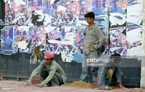 Iraqi laborers lay bricks in front of old election posters