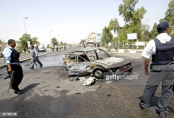 Iraqi policemen stand near the wreckage of car that was destroyed in a suicide car bomb explosion in alMansour district west of Baghdad 11 May 2005...