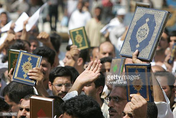 Iraqi protesters hold up copies of the Koran 16 September 2005 during a demonstration at the site of a suicide attack in the Shiite district of...