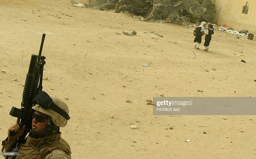 Iraqi schoolgirls play in their school playground as a US marine from the 6th Civil Affairs Group 2nd Marine Expeditionary Force (MEF) patrols the neighborhood in the city of Fallujah, west of Baghdad, 17 October 2005. More than 60 percent of the population returned to the city devastated by heavy combats between US marines and insurgents in November 2004. About 70 insurgents were killed in US air strikes in the Ramadi region of western Iraq, where five US and two Iraqi soldiers were killed in a weekend roadside bombing, the US military said today.