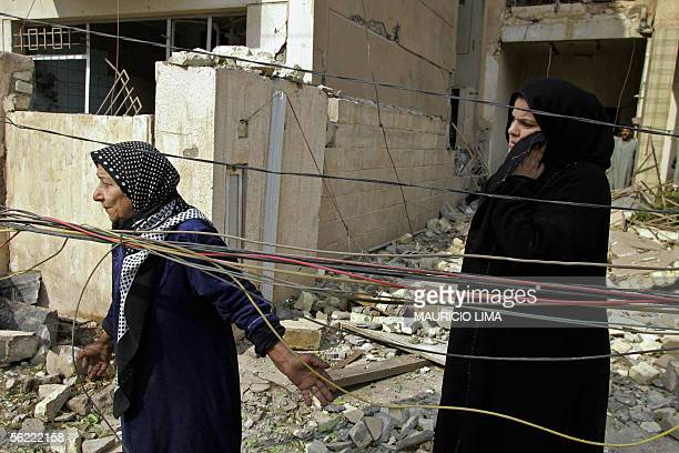 Iraqi women look at their destroyed residence at the site where two suicide bombers detonated explosivesladen cars near Al Hamra hotel that houses...
