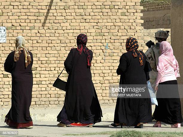 Iraqi women walk next to a US soldier from the Alfa Company 2/7 infantries division patrolling in Tikrit, 175 kms north of Baghdad, 24 September...