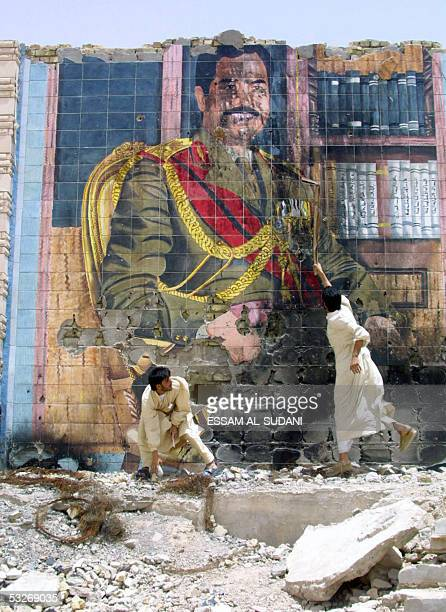 Iraqi youth beat with a stick a portrait of ousted dictator Saddam Hussein removed from power by USled coalition forces 09 April 2003 painted on a...