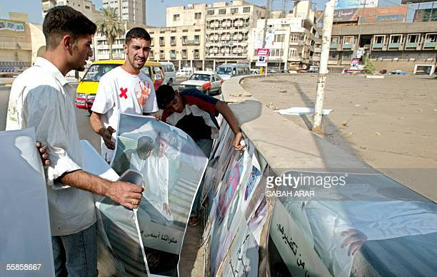 Iraqi youths paste posters denouncing terrorism on a wall in central Baghdad 06 October 2005 The posters show two Iraqis praying and a slogan that...