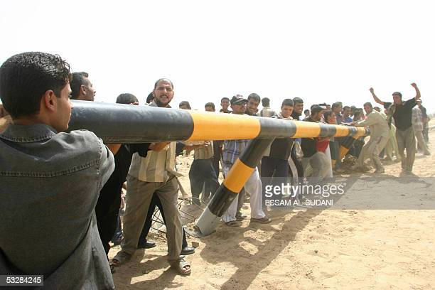 Iraqis are seen bringing down a barrier put up by Kuwait close to the town of Umm alQasr south of the city of Basra 25 July 2005 Several hundred...