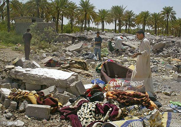 Iraqis search among the rubble 08 June 2006 of one of four houses believed to be destroyed by US forces in the town of Hibhib north of the restive of...