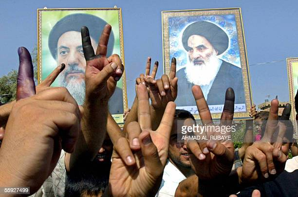 Iraqis show their ink-stained fingers and raise pictures of Grand Ayatollah Ali al-Sistani and late Mohammed Baqer al-Hakim as they jubilate in...