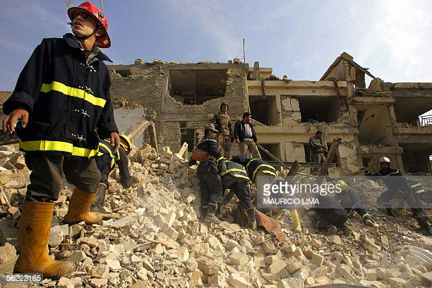 Members of Iraqi civil defense look for survives buried under the rubble of a destroyed house at the site where two suicide bombers detonated...