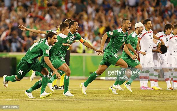 Iraq players run to congratulate Salam Shakir of Iraq on scoring the winning penalty during the 2015 Asian Cup match between Iran and Iraq at...