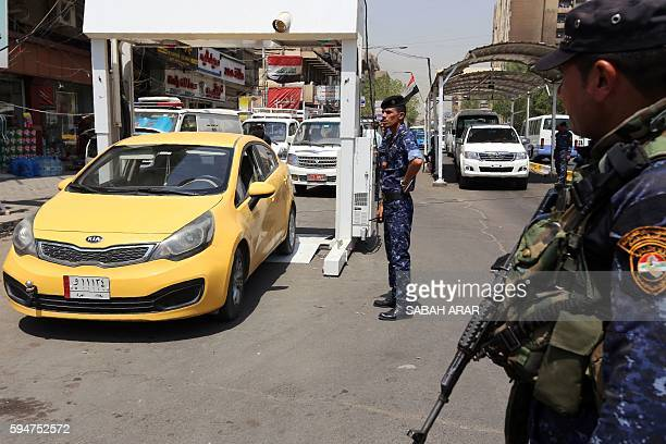 Iraq police monitor as cars drive through an Xray scanning system to detect explosives in Baghdad's Karrada district on August 24 near the site of...
