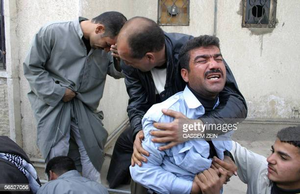 Relatives comfort each other after being told loved ones have been killed as they gather at the Husseini hospital following a suicide bomb attack in...