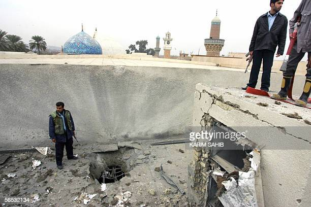 Security officers look at the damage caused to a section of the roof of a main Sunni Arab shrine the Abdul Kader alGilani shrine in central Baghdad...