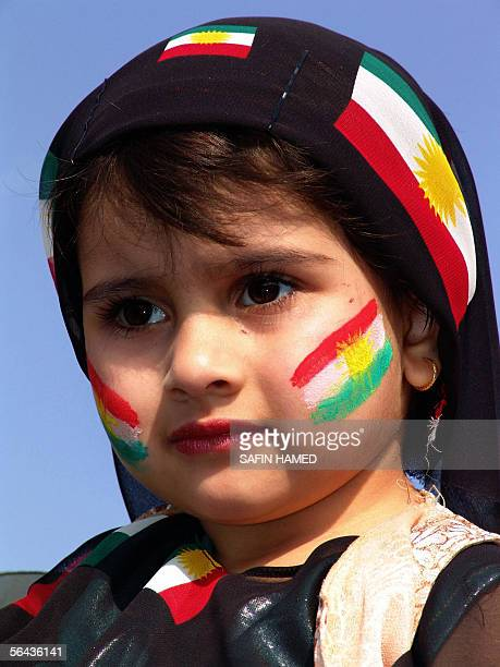 The cheeks of an Iraqi Kurdish girl are painted in the colors of the Kurdish flag as she waits with her family in line outside a polling station in...