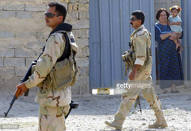 Two Iraqi soldiers secure the area as an Iraqi woman and her daughter look on during a raid by joint USIraqi forces 27 July 2005 near Baquba city in...