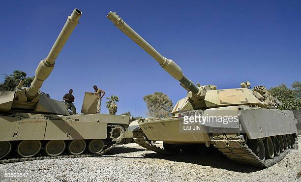 Two US soldiers of Delta Company Task Force 464 Armor work on the M1 Abrams Tanks at Camp Prosperity in Baghdad's fortified Green Zone 31 August 2005...