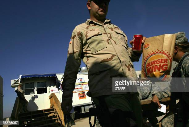 US Soldiers enjoy lunch at Burger King in their military base in southern Baghdad 08 December 2005 World Bank President Paul Wolfowitz suggested that...