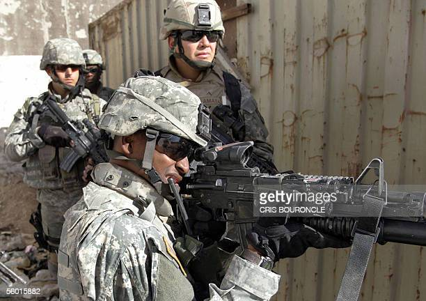 US Soldiers from the First Battalion 17th Infantry take cover against probable sniper fire behind a metal container as they advance in an industrial...
