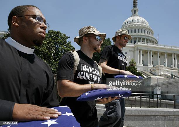 Iraq Veterans Against the War members Rev Lennox Yearwood Adam Kokesh and Garett Reppenhagen walk with folded US flags past the US Capitol July 17...