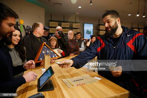 Iraq War veteran Stephen Mandile of Uxbridge hands his money to Cultivate President Sam Barber as he makes the first purchase at the opening of...