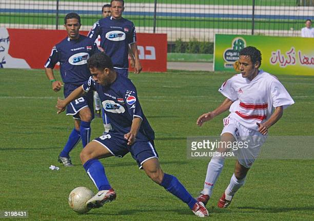 Iraqi AlTalaba club player Saleh Sadeer is chased by Egyptian AlZamalek club player Tarek AlSayyed during their Arab Champions League quarterfinal...