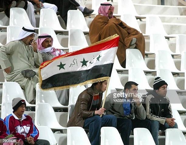 Iraqi alTalaba fans holds the Iraqi flag in Kuwait City for the first time since Kuwait was liberated from Iraqi occupation in 1990 during their...