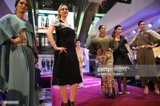 Iraqi and Iranian models present outfits designed by two Iranian female designers at the end of a fashion show at a shopping mall in the Iraqi...