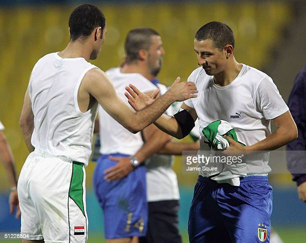 Iraqi and Italian football players exchange jerseys after competing in the men's football bronze medal match on August 27 2004 during the Athens 2004...