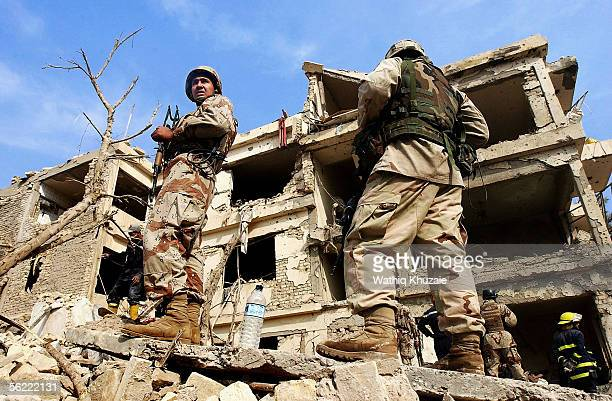 Iraqi and US soldiers stand on the rubble where two suicide car bombs exploded near Alhamra hotel on November 18 2005 in Baghdad Iraq Two suicide...