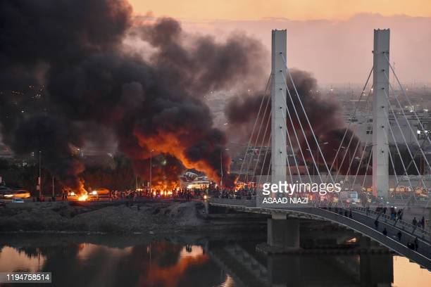 Iraqi Anti-government demonstrators block a bridge with debris and burning tires in the southern Iraqi city of Nasiriyah on January 19, 2020.