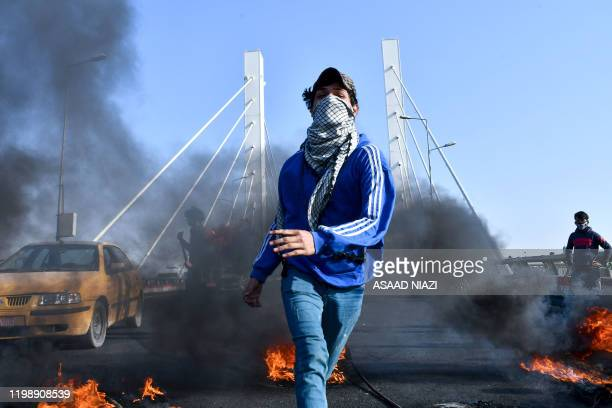 Iraqi antigovernment protesters burn tyres to block the bridge of civilizations in the southern city of Nasiriyah on February 6 2020 Antigovernment...