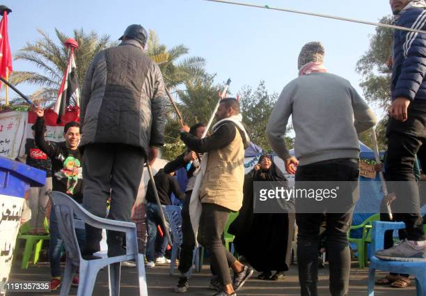 Iraqi anti-government protesters celebrate outside their protest tents in Baghdad's Tahrir Square following news of the killing of Iranian...