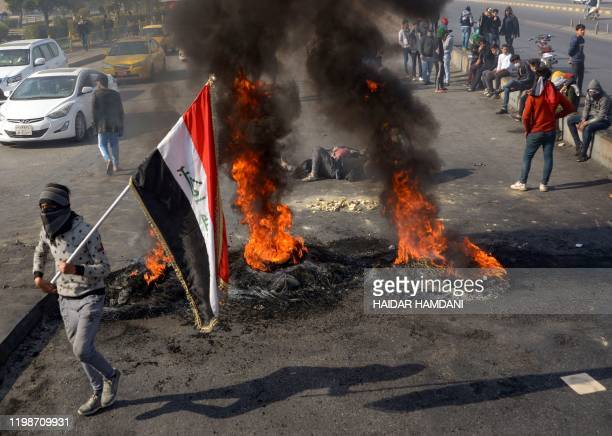 Iraqi antigovernment protesters cut off a road with burning tyres in the central holy shrine city of Najaf during a demonstration against followers...