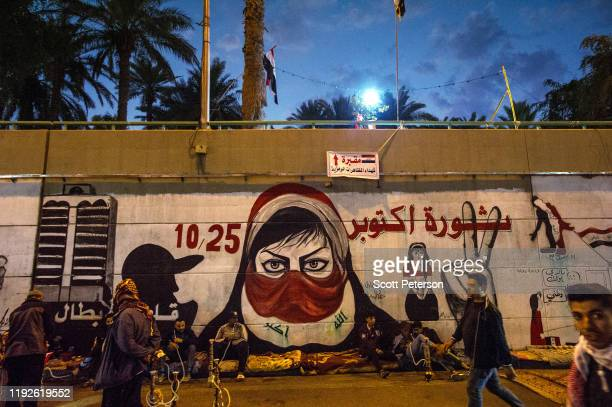 Iraqi anti-government protesters drape themselves with flags, paint graffiti, and mourn their martyrs in Tahrir Square as nationwide protests entered...