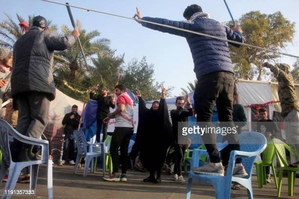 Iraqi antigovernment protesters flash the Vsign of victory outside their protest tents in Baghdad's Tahrir Square following news of the killing of...