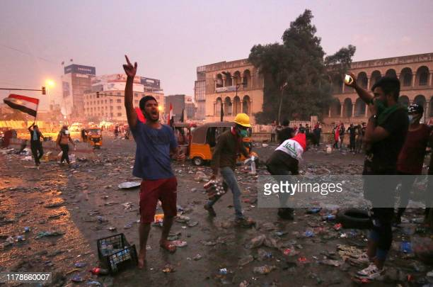 TOPSHOT Iraqi antigovernment protesters shout slogans after security forces fired tear gas to keep demonstrators from storming the Green Zone which...