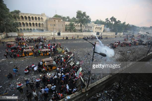 TOPSHOT Iraqi antigovernment protesters take cover from security forces firing tear gas to keep demonstrators from storming the Green Zone which...