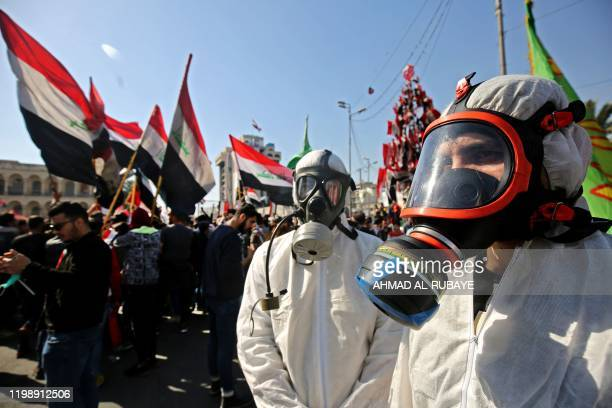 Iraqi anti-government protesters wearing hazmat suits and gas masks take part in a student demonstration in the capital Baghdad's Tahrir square, on...