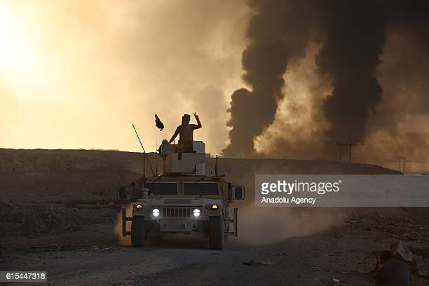 Iraqi army forces arrive in Hut village as smoke rises from oil wells were set on fire by Daesh terrorists to limit coalition forces pilots' eyesight...