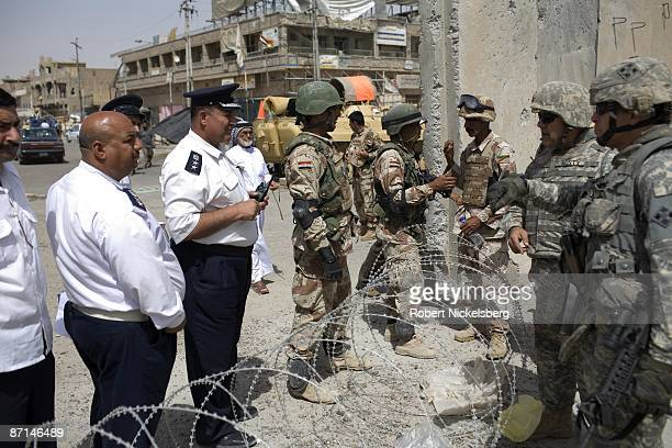 Iraqi Army soldiers and National Policemen left speak with US Army soldiers right to clarify crossing guidelines as civilians cross the concrete...