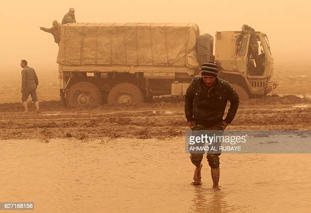 TOPSHOT Iraqi army soldiers attempt to move their truck stuck in the mud near the village of AlBoutha alSharqiyah west of Mosul on December 2 during...