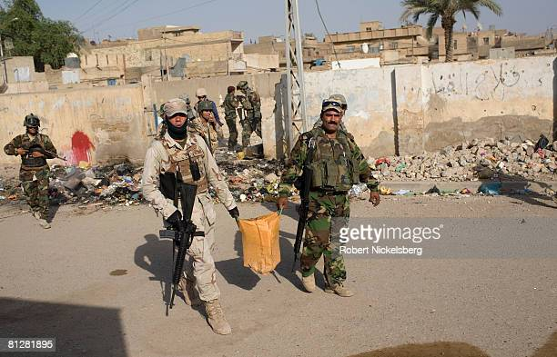 Iraqi Army soldiers carry out a large IED hidden by militias inside a generator room in the southern part of Sadr City a Shiite militant stronghold...