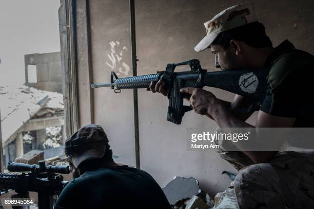 Iraqi Army soldiers fire at an Islamic State sniper position June 17 2017 in alShifa the last district of west Mosul under Islamic State control IS...