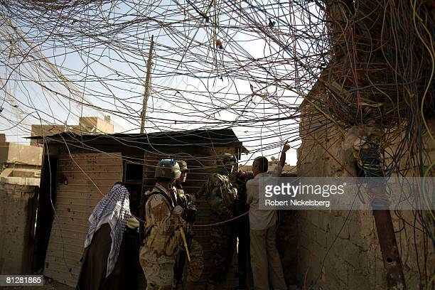 Iraqi Army soldiers help local Shiite residents of Sadr City remove a large IED hidden by militias inside a generator room in the southern part of...