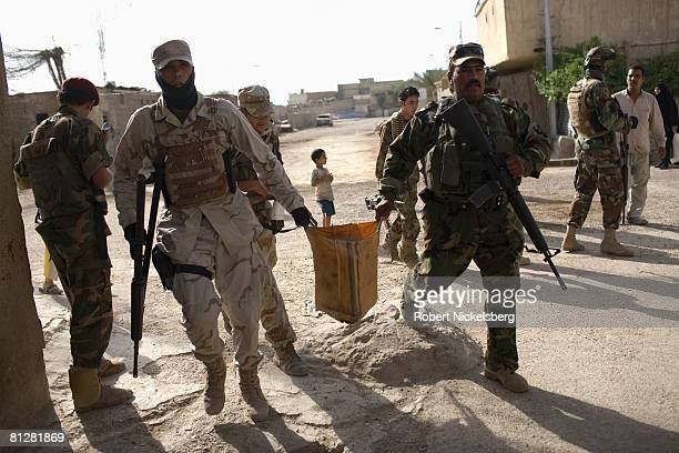 Iraqi Army soldiers in Sadr City remove a large IED hidden by Shiite militias inside a generator room upper left in the southern part of Sadr City a...